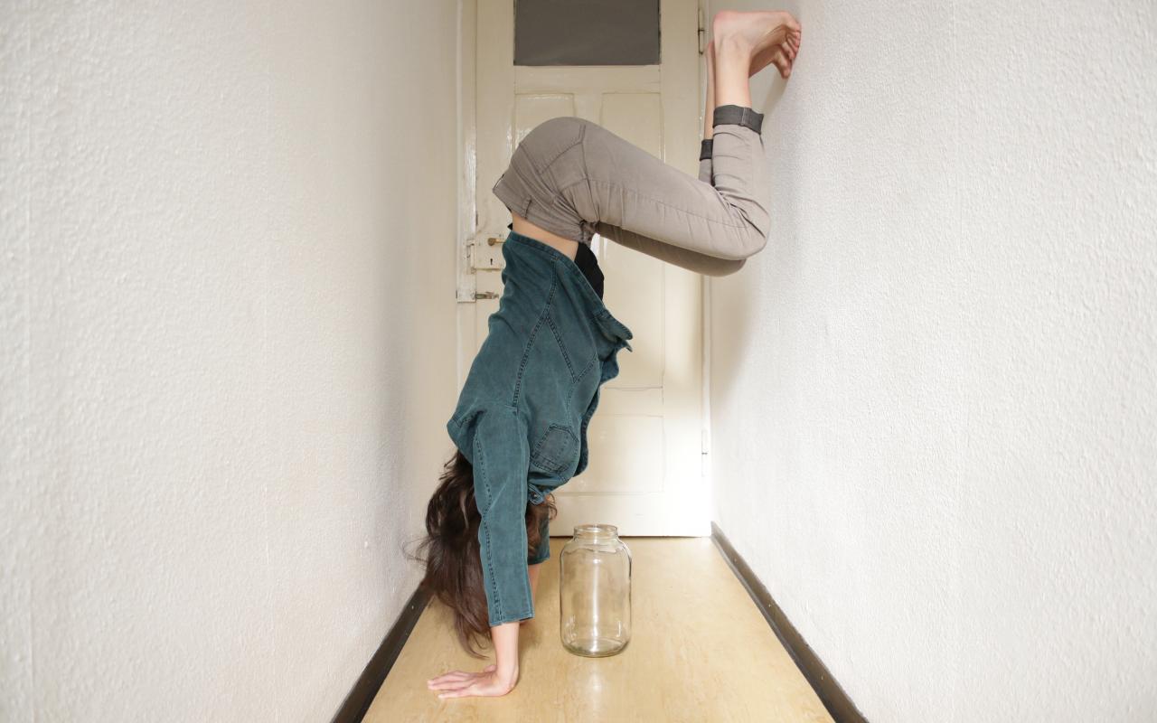 Eine Person macht einen Handstand an der Wand in einem schmalen Gang, unter ihr steht ein leeres Glasgefäß.