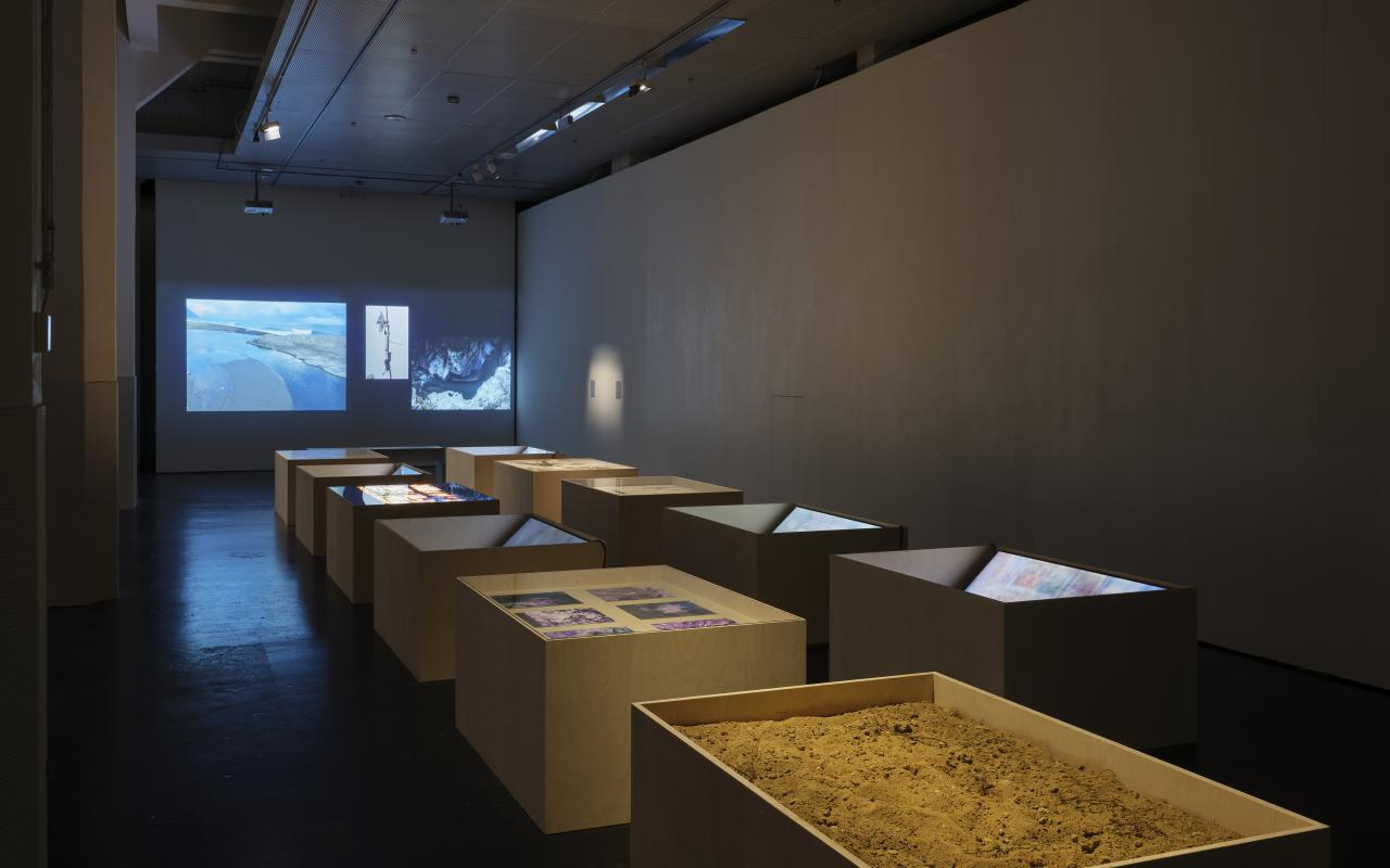 You can see large showcases in front of a white wall. In the showcases are screens with videos and photos.