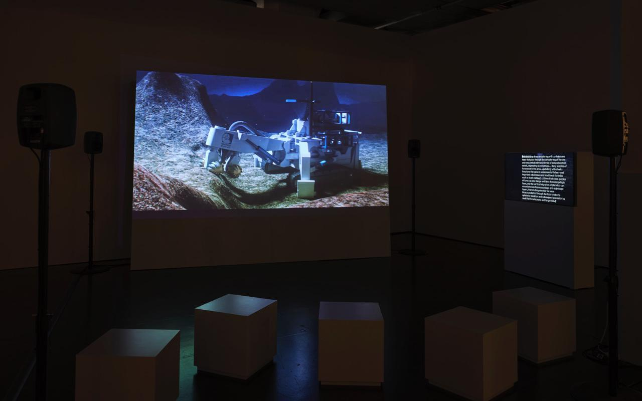 The picture shows a room with seating boxes, monitors and a large screen on which the film »Prospecting Ocean« by Armin Linke is played.