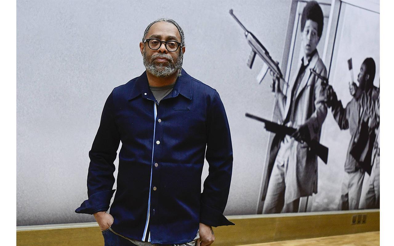 Arthur Jafa steht vor einer Wand, auf der eine Fotografie mit zwei jungen Afroamerikanern mit Waffen abgebildet ist.