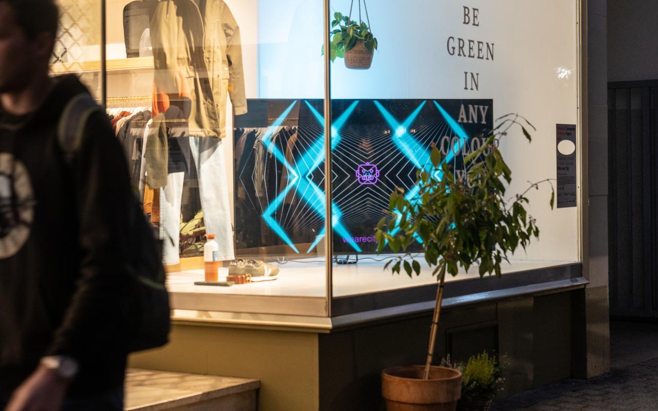 Die interaktive Lichtinstallation wird auf einem großen Bildschirm gezeigt, welcher sich im Schaufenster eines Bekleidungsgeschäftes befindet.