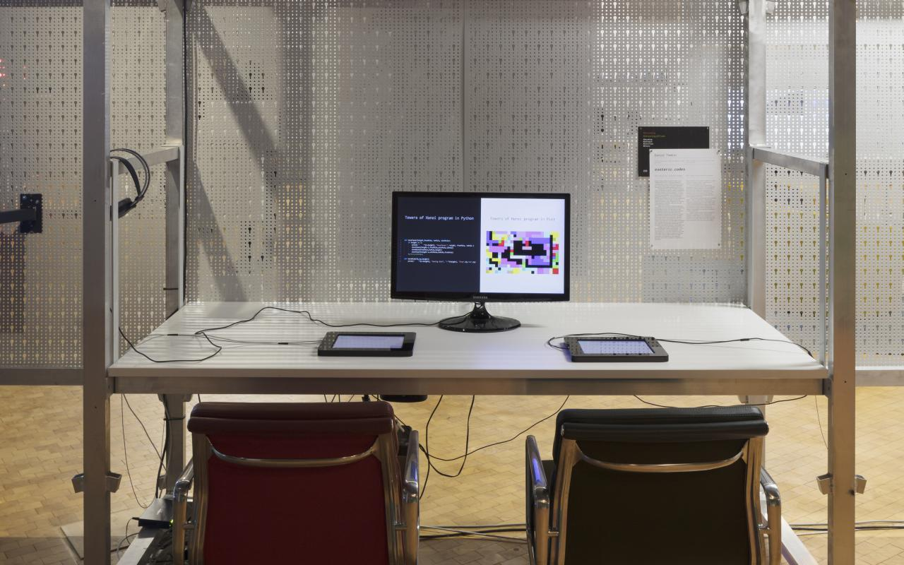 A desk with monitor and two chairs