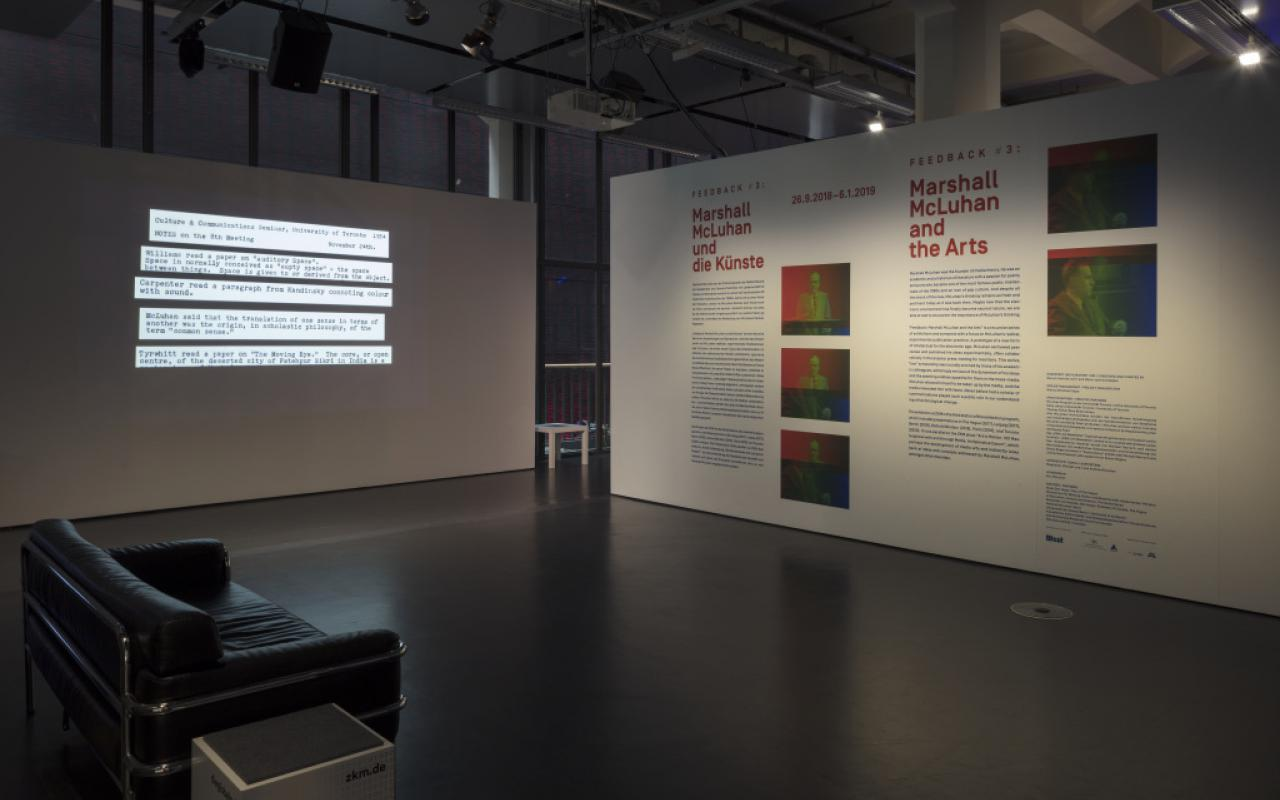 In the foreground on the left side is a black sofa. At the back left there is a partition wall with text projection. In the back on the right there is a wall printed with text and pictures.