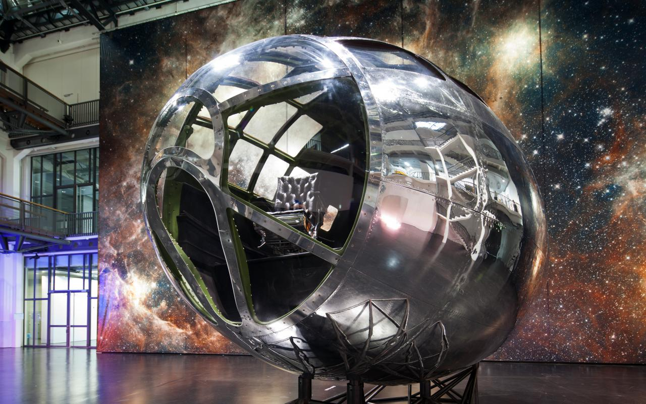 You can see a silver frame, reminiscent of a rocket top, standing in front of a large canvas with a motif of a galaxy. In the front glass dome of the frame you can see a black leather armchair.