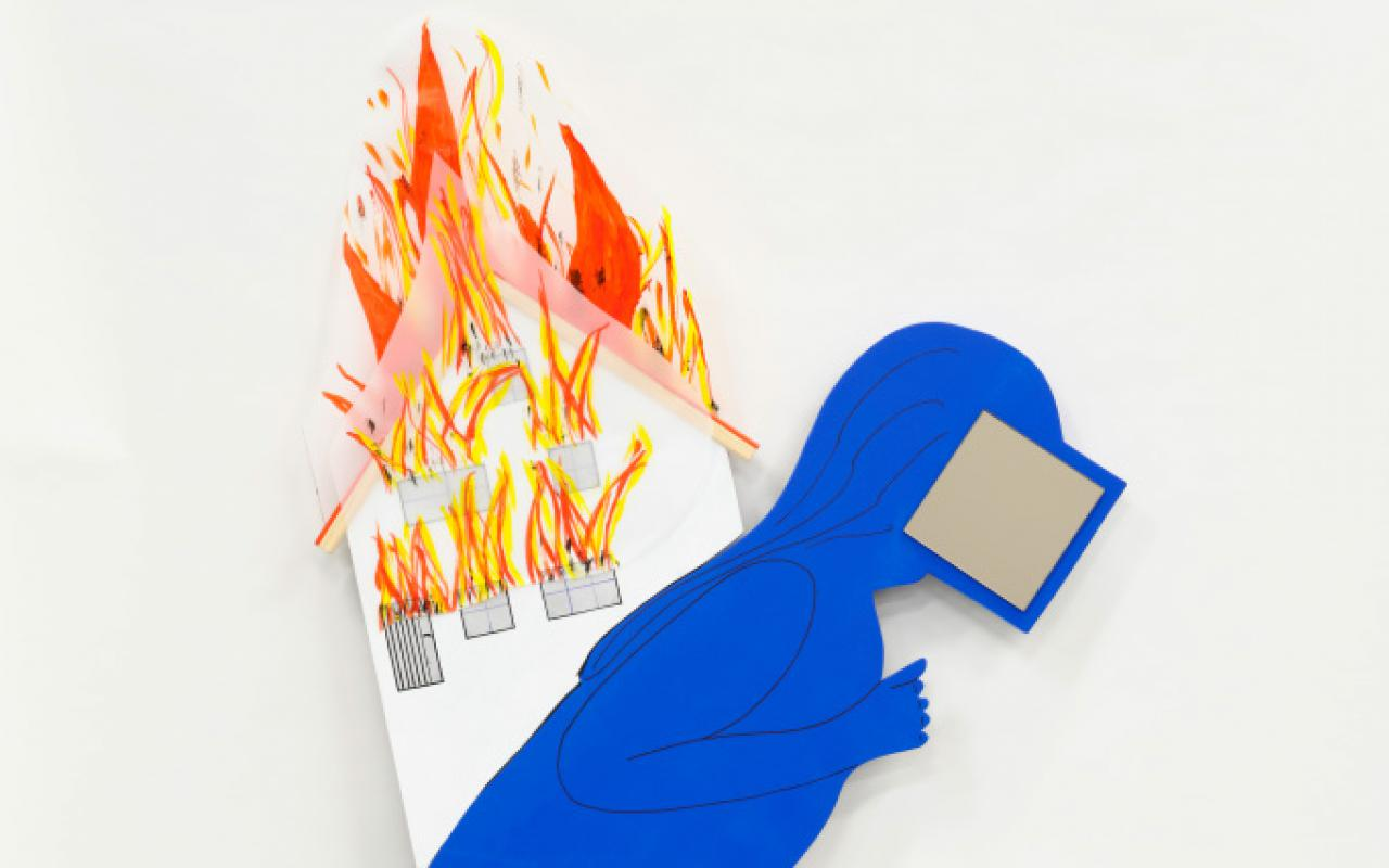 A stooped figure with a screen in front of his face and a blue mask carries a burning house on his shoulders. Stars are woven into the edge of the blue robe and at waist level.