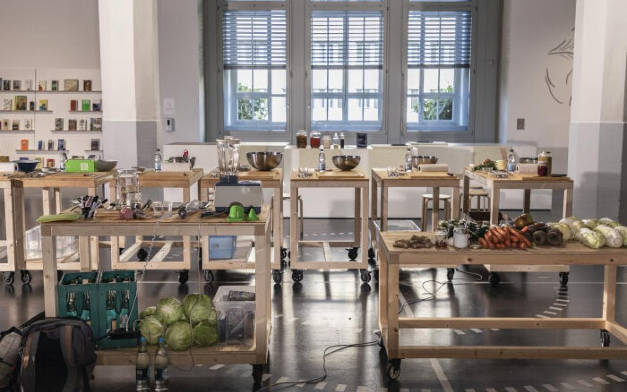 There are wooden tables with food and kitchen tools standing in the ZKM exhibition »Critical Zones«.