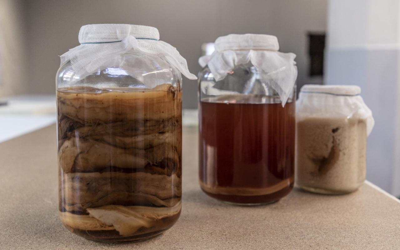 Three preserving jars on a wooden table with different contents