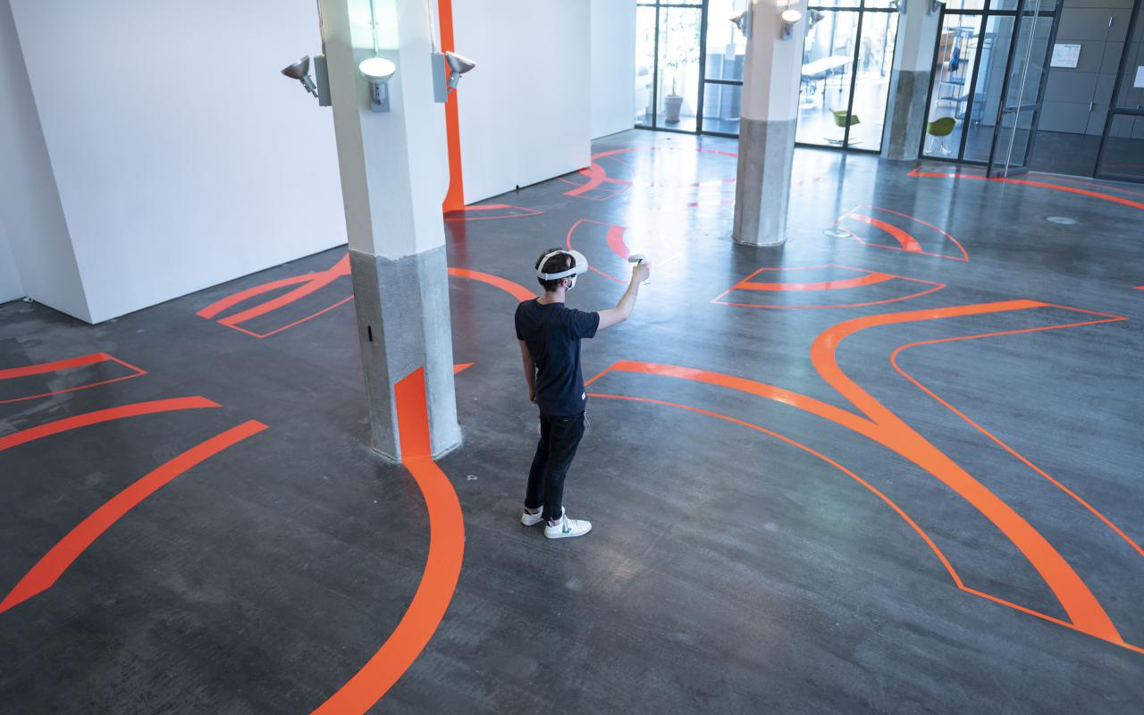A man wears VR goggles and stands amid thick lines taped to the floor and walls.