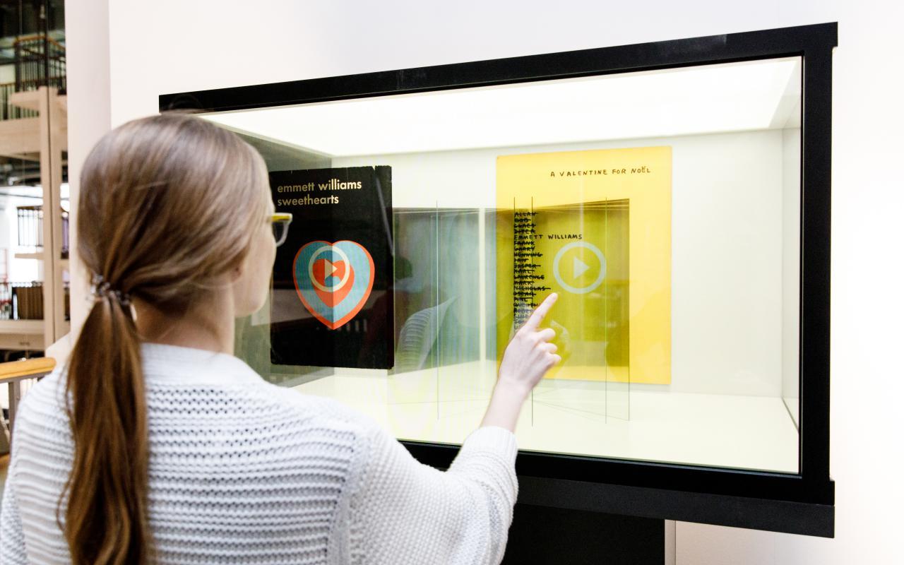 Eine Frau steht vor einer gläsernen Box in der sie Bücher mit ihren Fingern auswählen und lesen kann