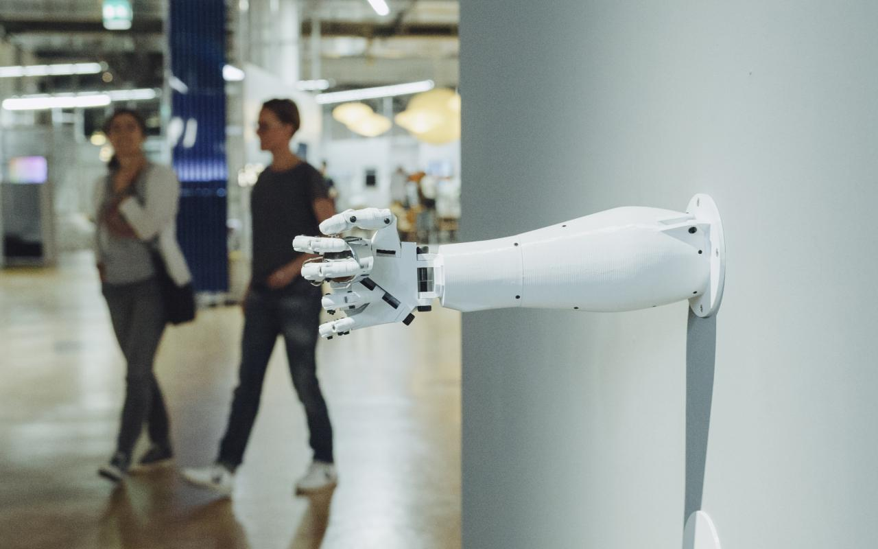 A robot arm protrudes from a wall whose hand holds something enclosed.