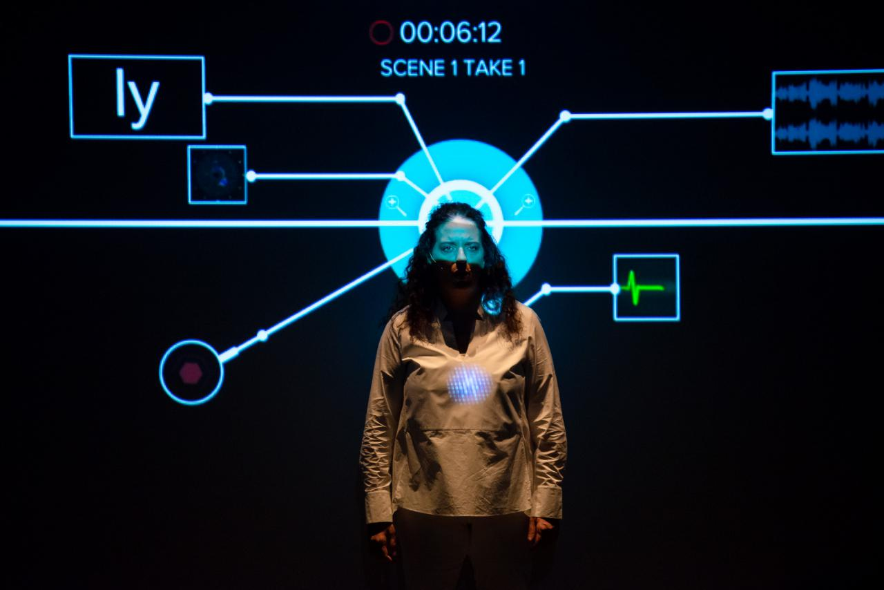 Noa Frenkel is standing in front of a projection. Her head is exactly in front of a circle and from this circle a mapping flows out in all directions.