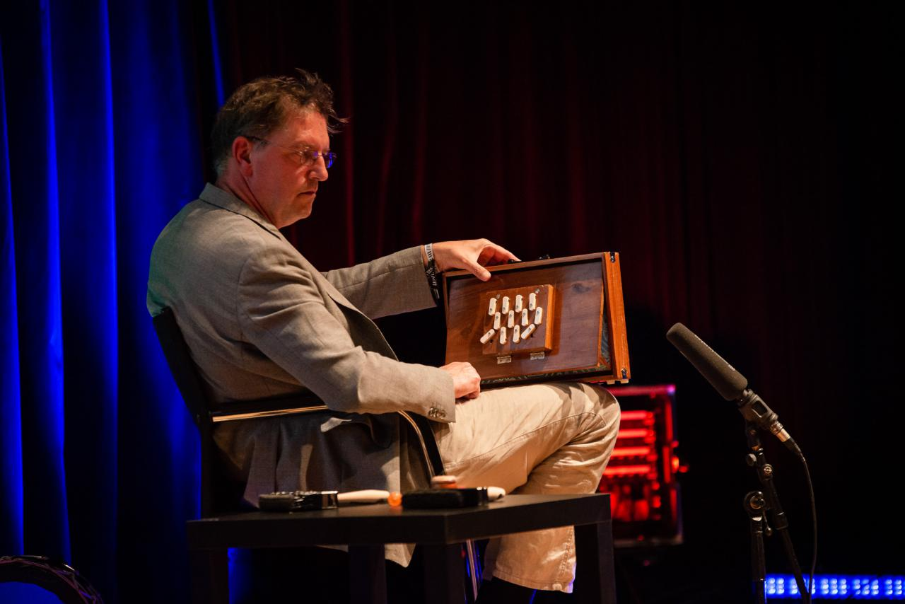 Manos Tsangaris creates sounds on a curious wooden instrument that resembles a combination of box and accordion.