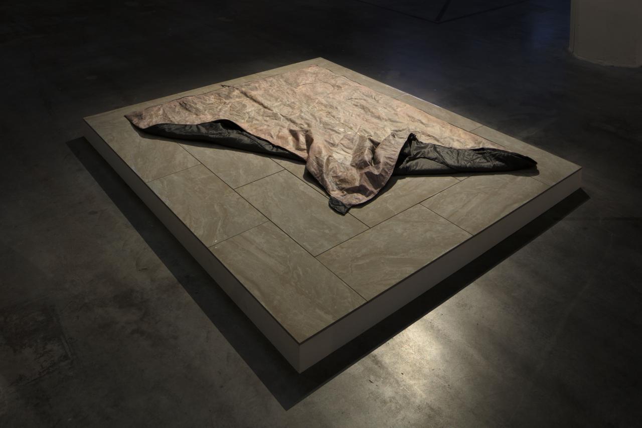 Auf einer Steinplatte liegt eine Decke.
