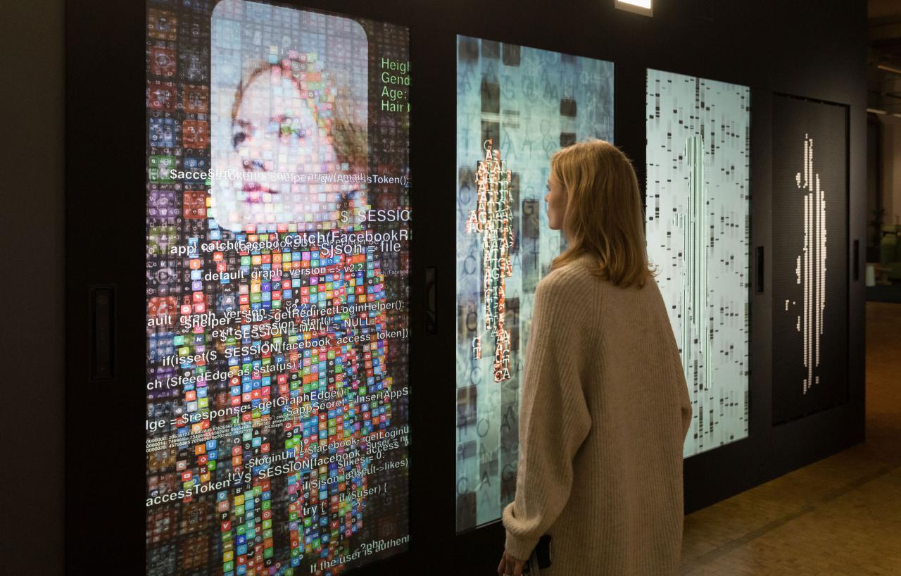 Eine Frau steht vor einer Wand mit mehreren Bildschirmen und digitalen Darstellungen
