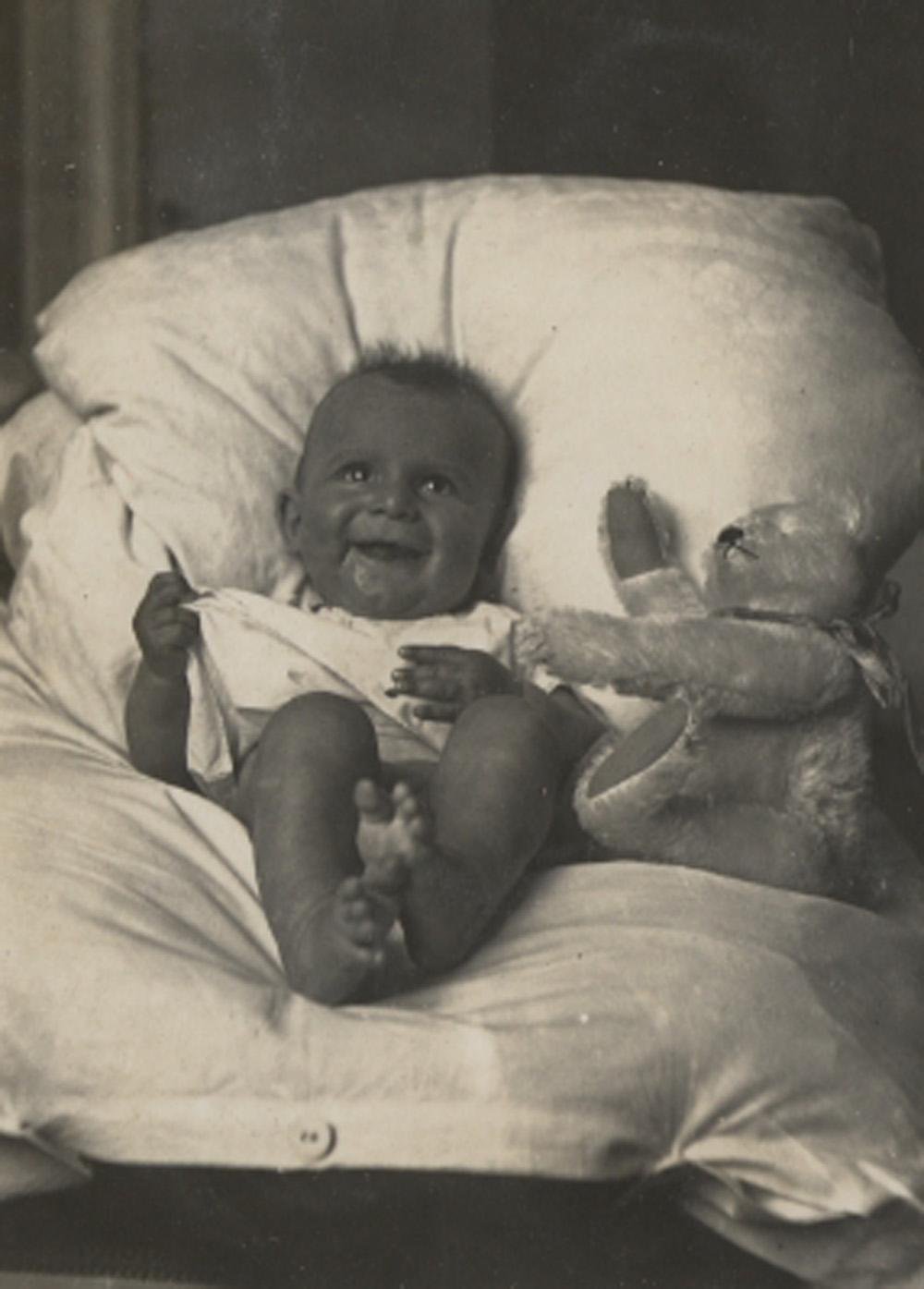 Ein Baby mit Teddybar, auf einem weissen Kissen liegend.