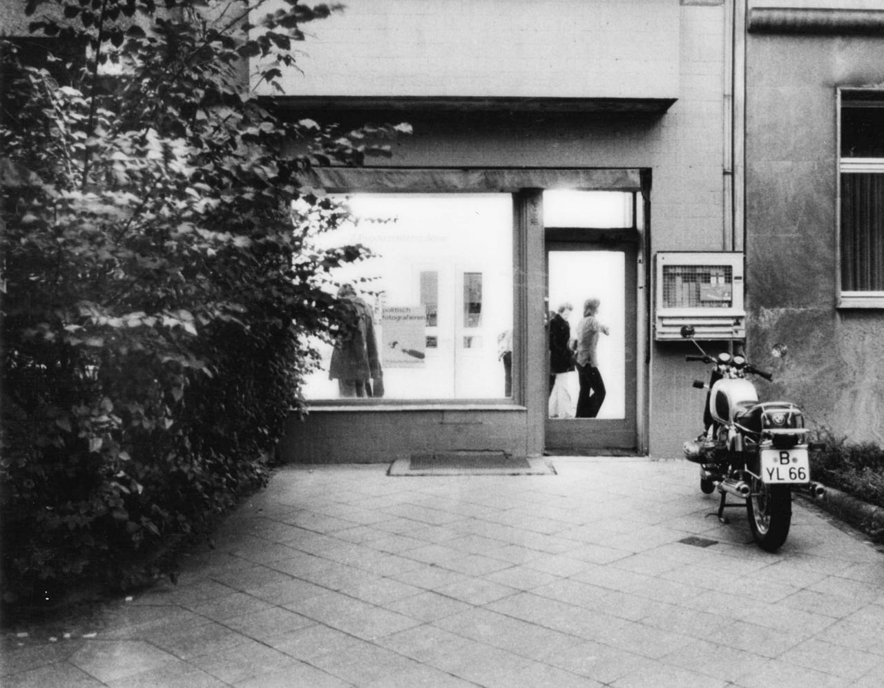 Schwarz-weiß Foto zeigt die Straßenansicht eines Galerieraum. Davor steht ein Motorrad.