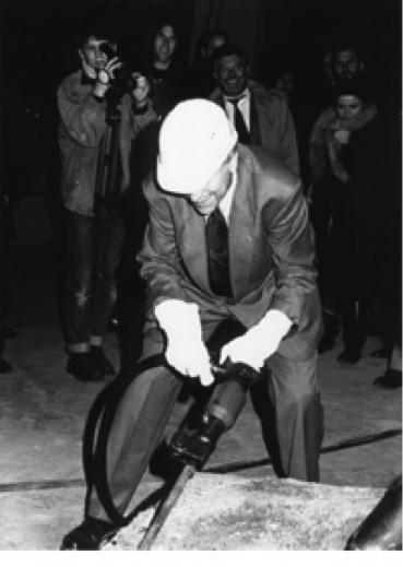 Ein Mann mit Bauarbeiterhelm und Druckluft-Meißel in den Händen.