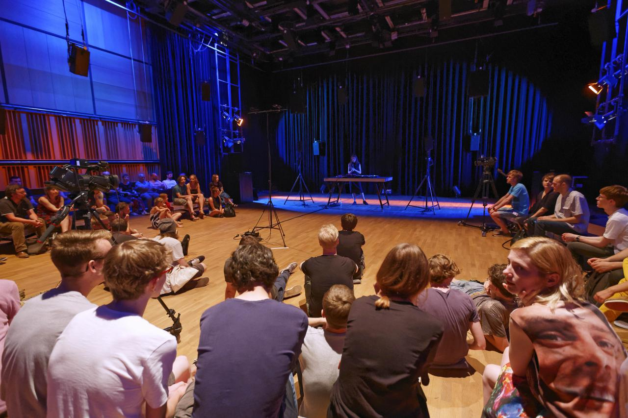 Menschen sitzen auf dem Boden vor einer Bühne, auf der eine Frau steht