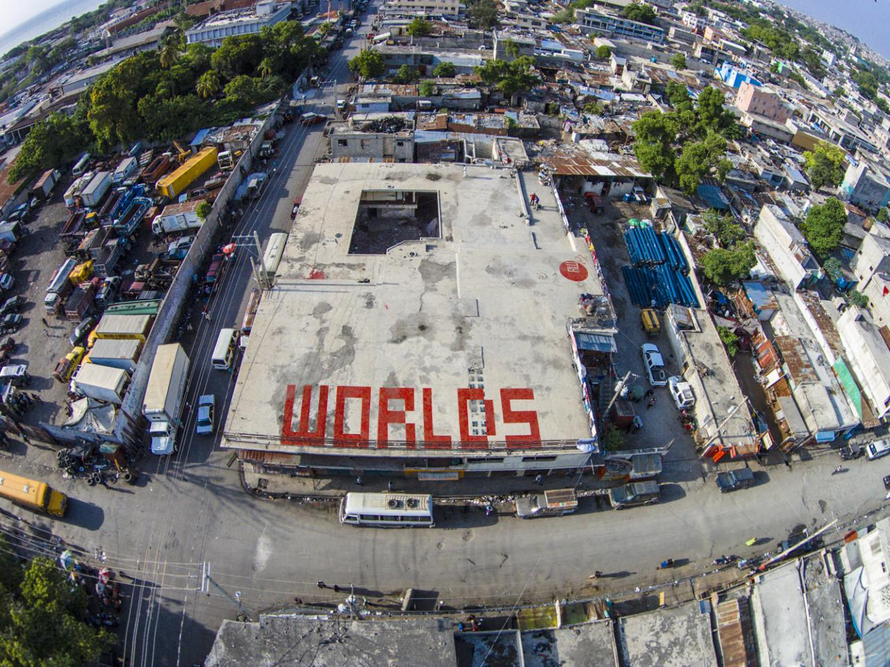 """The word """"worlds"""" written in big red letters on a roof top in haiti, view from above"""