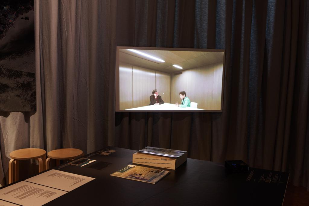 Tisch mit Exponaten und Hockern im Vordergrund, ein Bildschirm im Hintergrund.