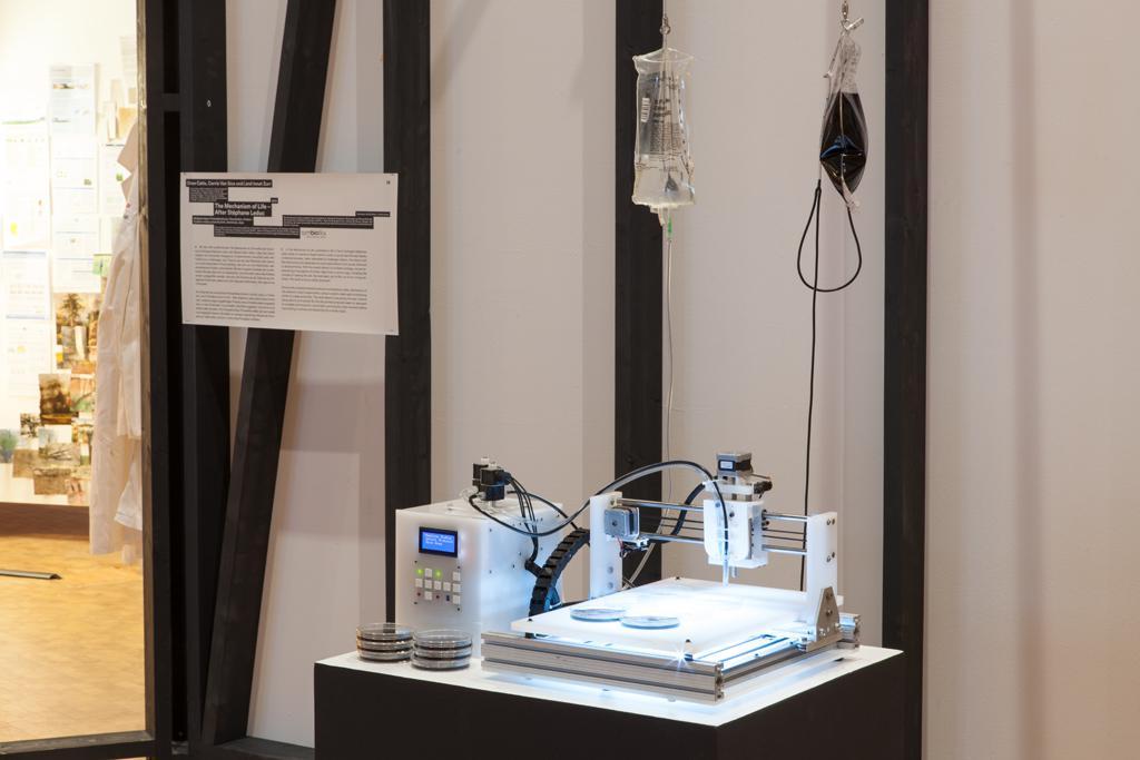 Schnelldrucker und Petrischalen auf einem Sockel, zwei verschiedene Infusionsbeutel hängend darüber.