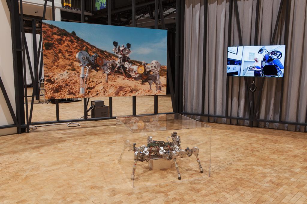 Ein Roboter steht im Vordergrund auf dem Boden, er wird von einer Glashaube abgedeckt. Ein großformatiger Fotodruck und ein Monitor mit Kopfhörern hägen an der Wand.
