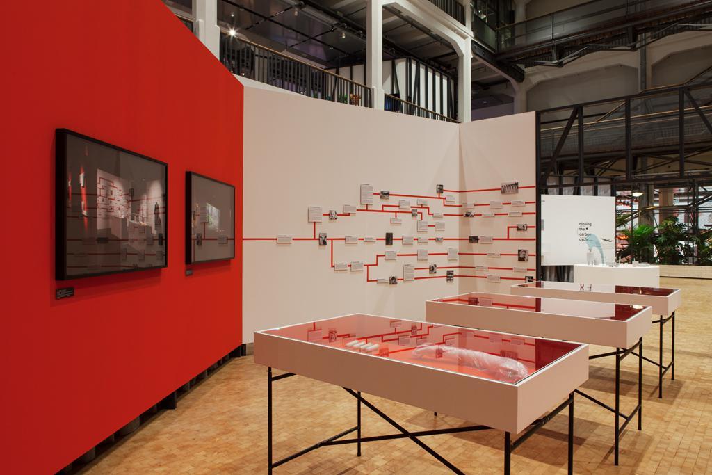 Zwei Bilder an einer rorten Wand, daran anschließend werden kleine Bilder und Texte 2auf einer weißen Wand mittels rotem Pfand strukturiert. Im Vordergrund stehen drei Tischvitrienen.