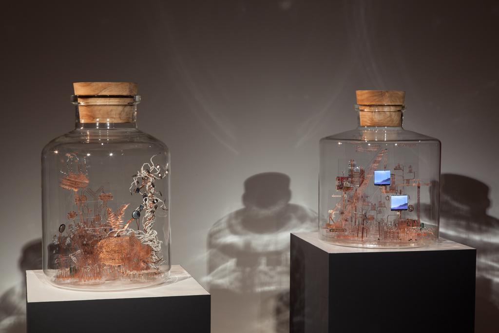 Auf zwei Sockeln steht jeweils eine Glasbehälter. In den Gefäßen befinden sich Modelle aus feinem Kupferdraht und anderen elektrotechnischen Materialien.