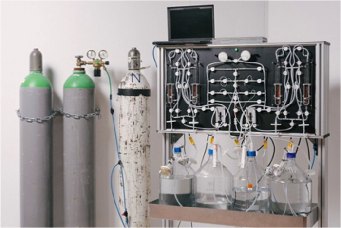 Eine Apparatur mit drei Gasflaschen links und Kolbengläsern in der Mitte