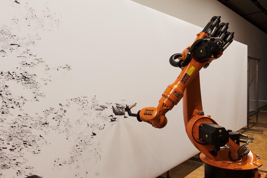 Ein Industrieroboter zeichnet ein mit einem Stift auf ein Großformat