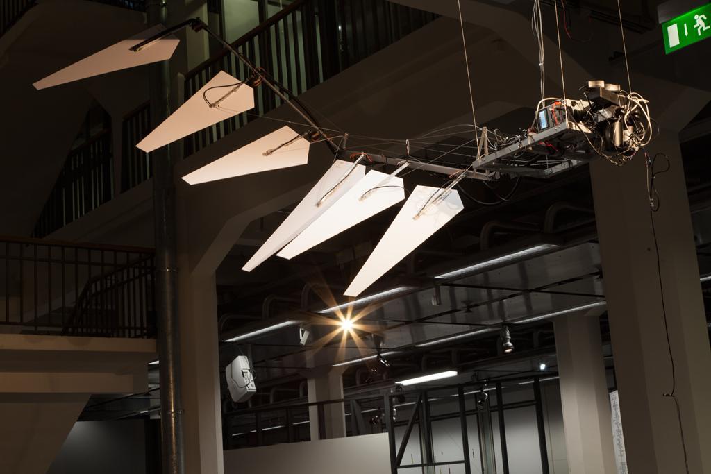 Hängendes Gestänge aus Metall, daran angegliedert sechs weiße Blätter in Federform. Die einzelnen Elemente sind zusätzlich elektrotechnisch mit einander verbunden.