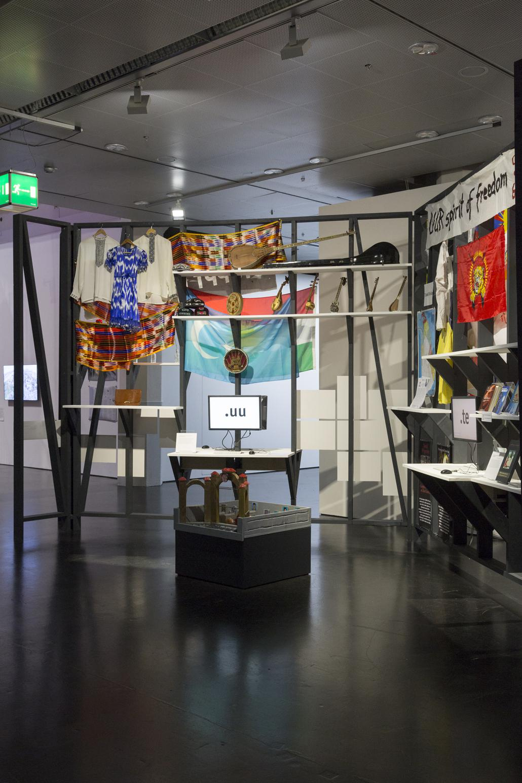 Clothes, instruments and books are hanging and standing at a wall