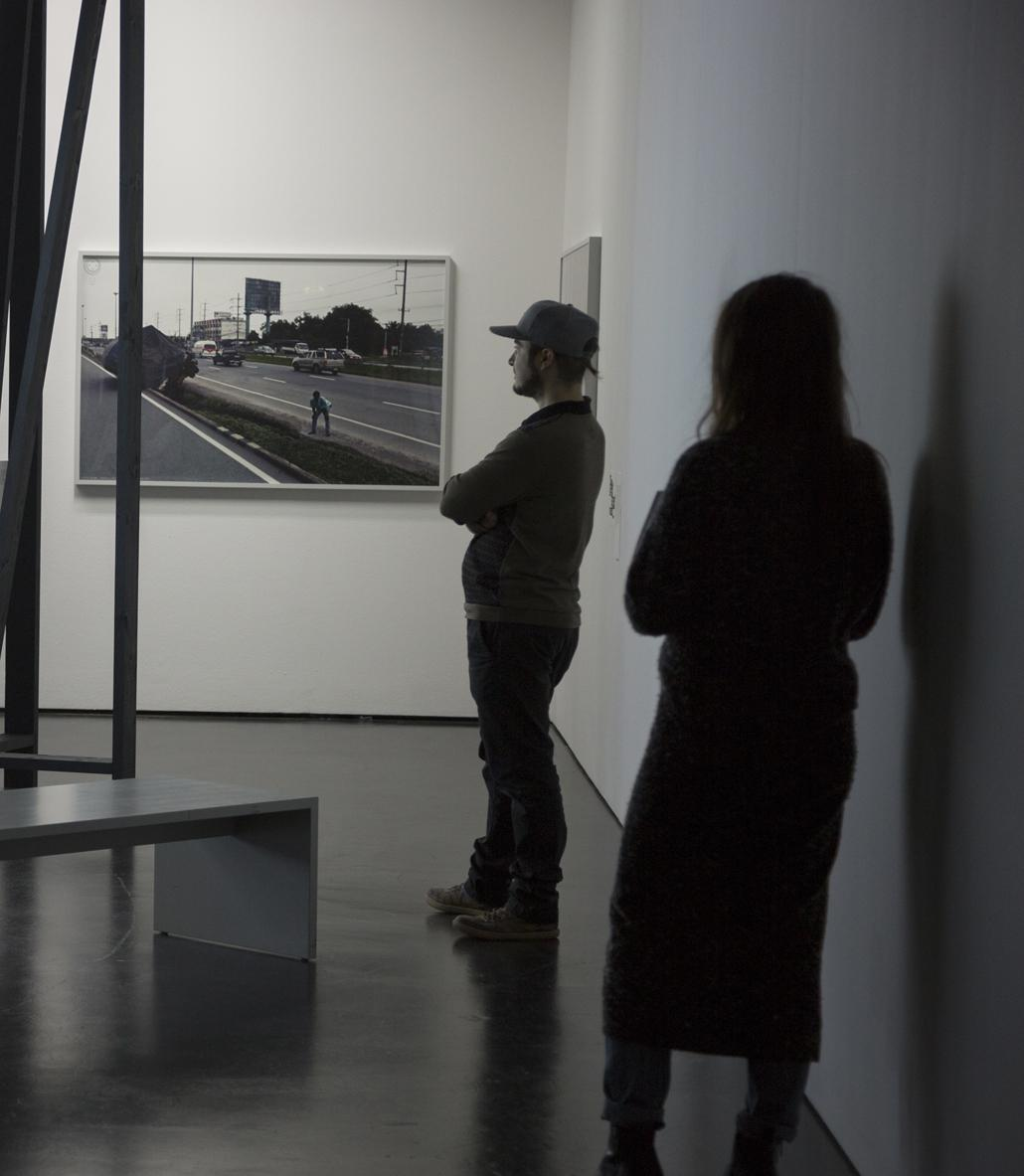 Two persons look at a picture at the wall