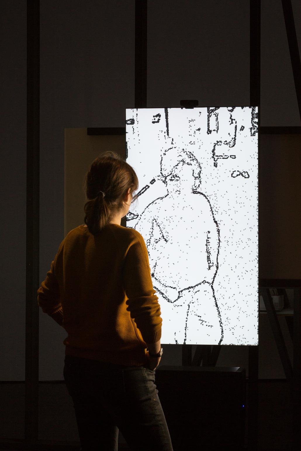 A person stands in front of a drawing of a person