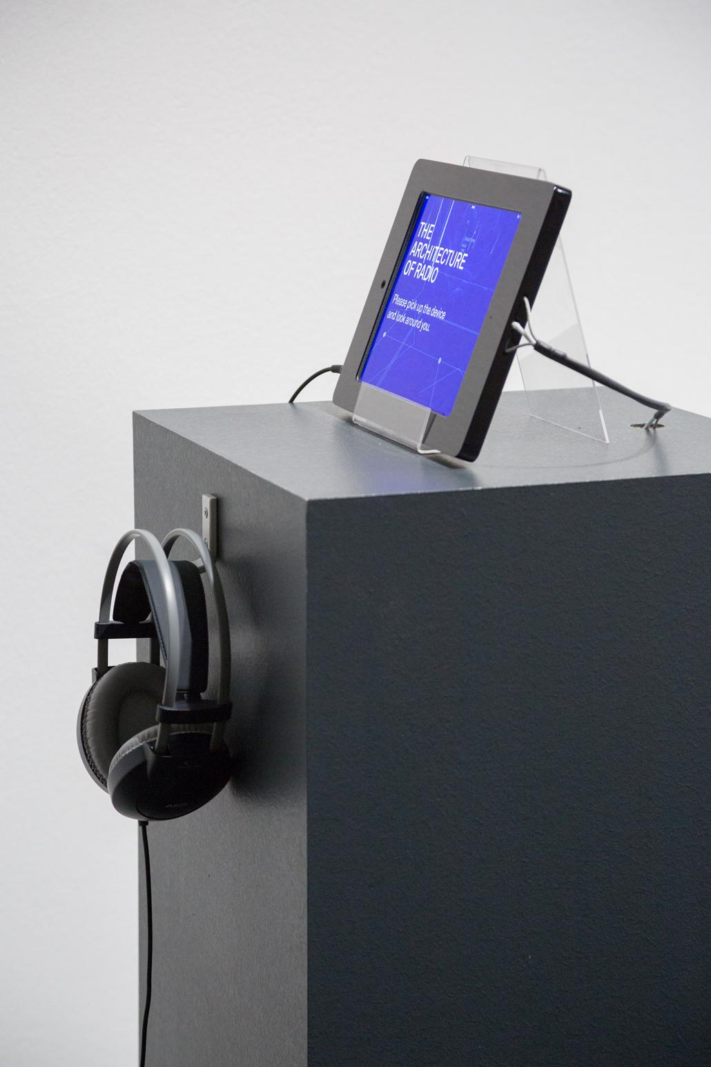 A pedestal on which a tablet stands and headphones hanging