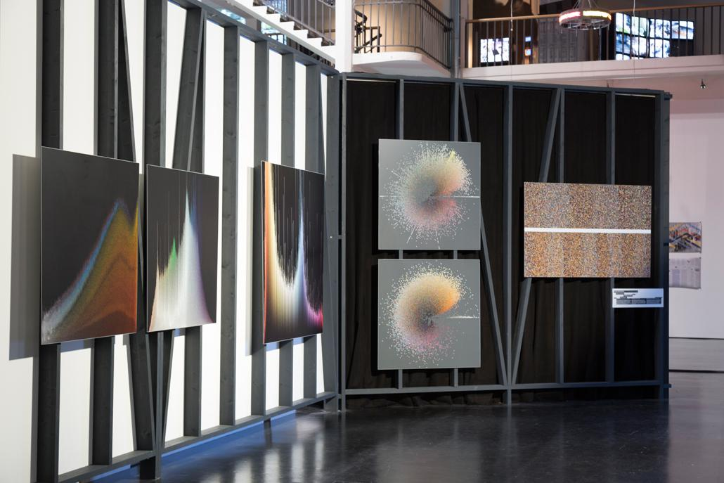 Canvases with colorful sine curves and circles on the wall