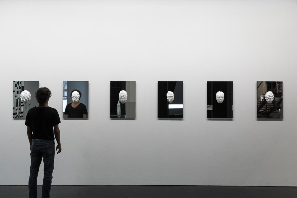In Gips gegossene Masken, die an Spiegeln hänge
