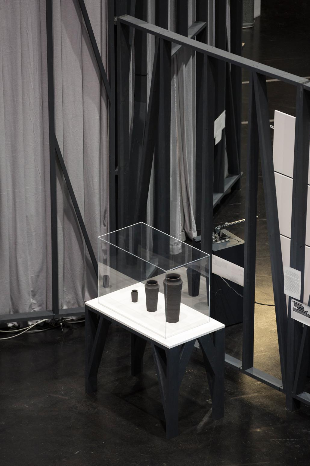 Three gray vases in different sizes in a showcase