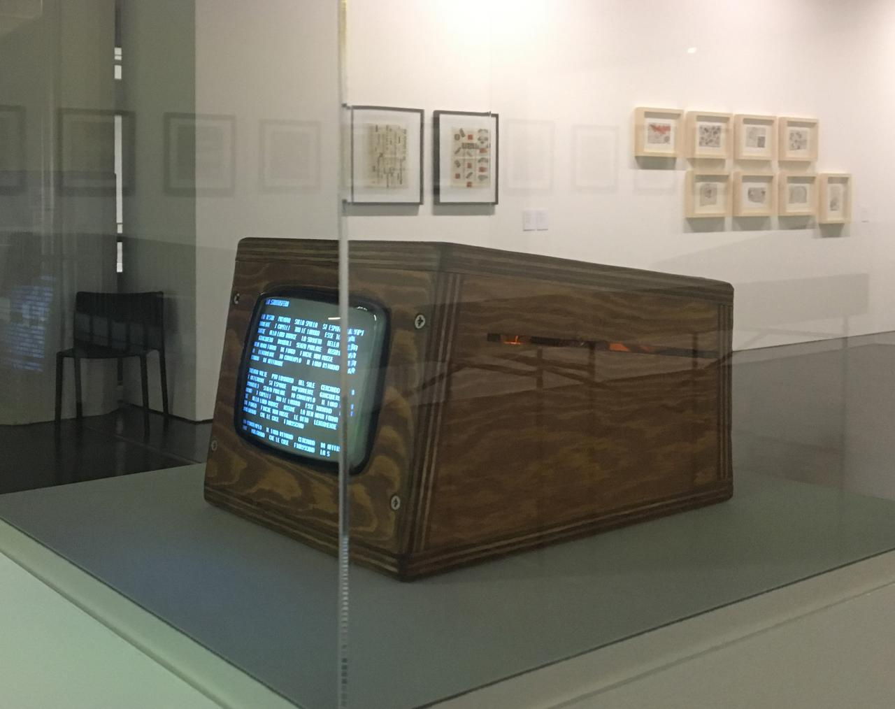"""Photo of the reconstruction of the poem """"Tape Mark I"""" by Nanni Balestrini: a small wooden box with a screen"""
