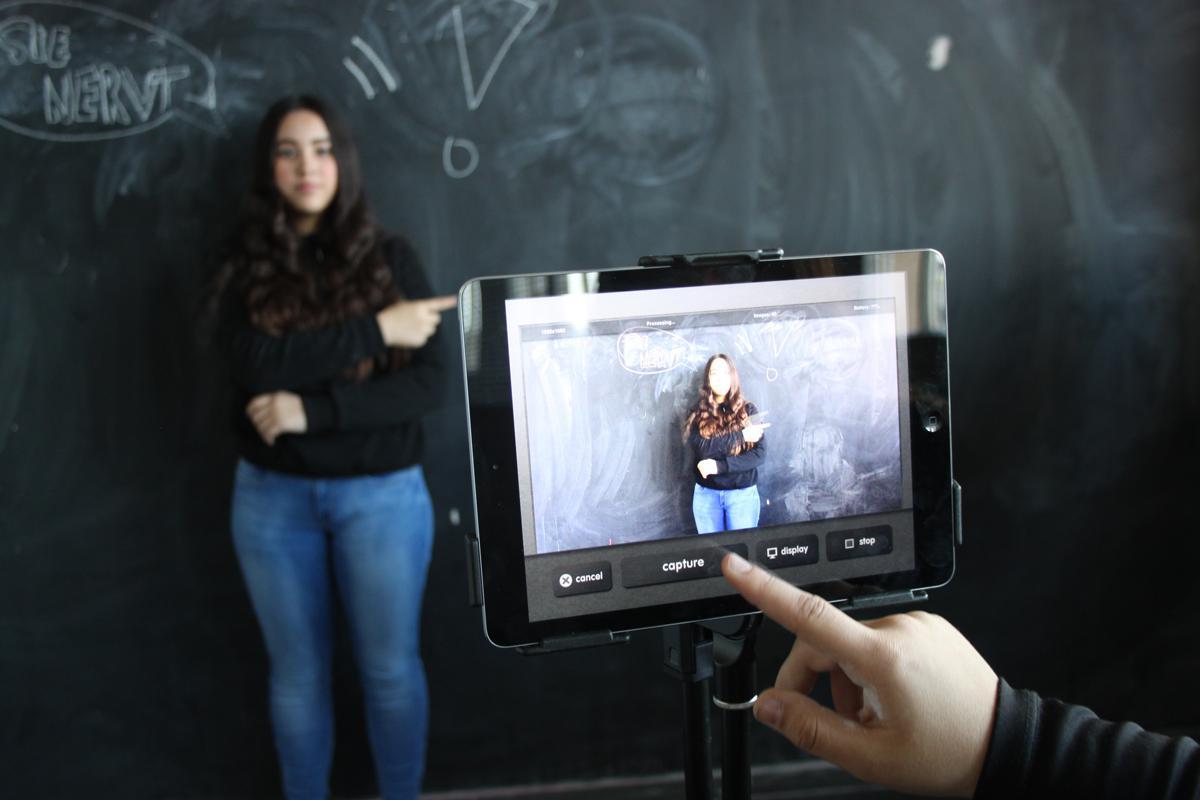 Ein Mädchen, das vor einer Tafel steht, wird mit einem Tablet fotografiert.