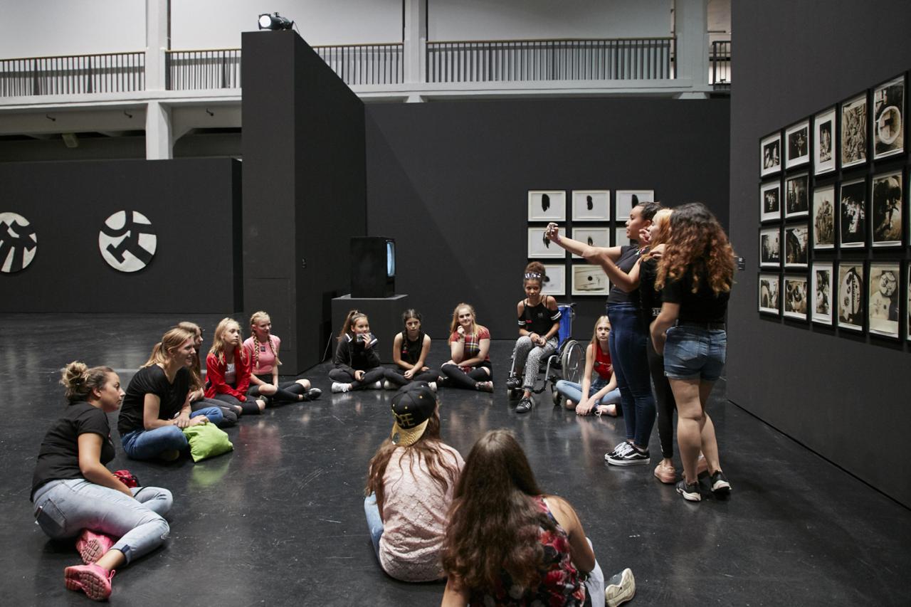 Eine Gruppe von Mädchen sitzt im Kreis in einer Ausstellung. Drei von ihnen machen ein Selfie vor einem Kunstwerk.