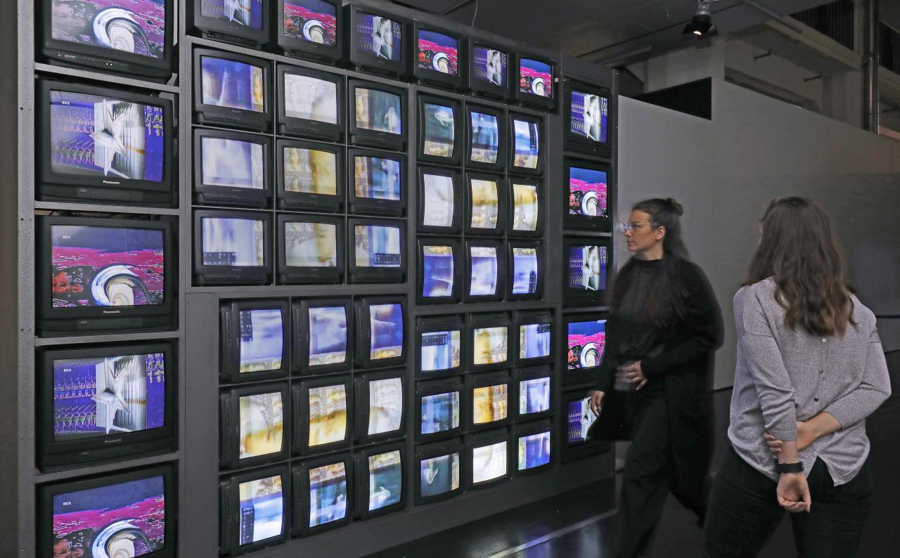 Besucherinnen vor einer Installation aus 52 Monitoren, die eine bunte Bildchoreografie zeigen.
