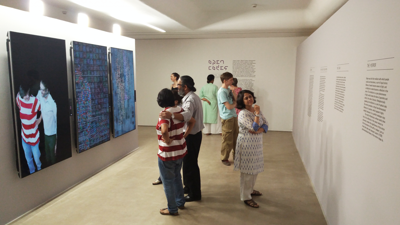 A group of people is standing in an exhibition space with white walls, reading the exhibition's texts or interacting with an installation.