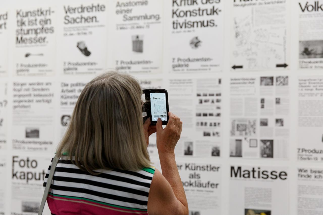 Eine Besucherin fotografiert mit Ihrem Smartphone eine Wand voller Typographie-Plakate.