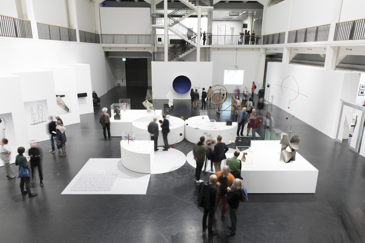 Viele Menschen befinden sich in Lichthof 8 und schauen sich die Kunstwerke der Ausstellung »Negativer Raum« an