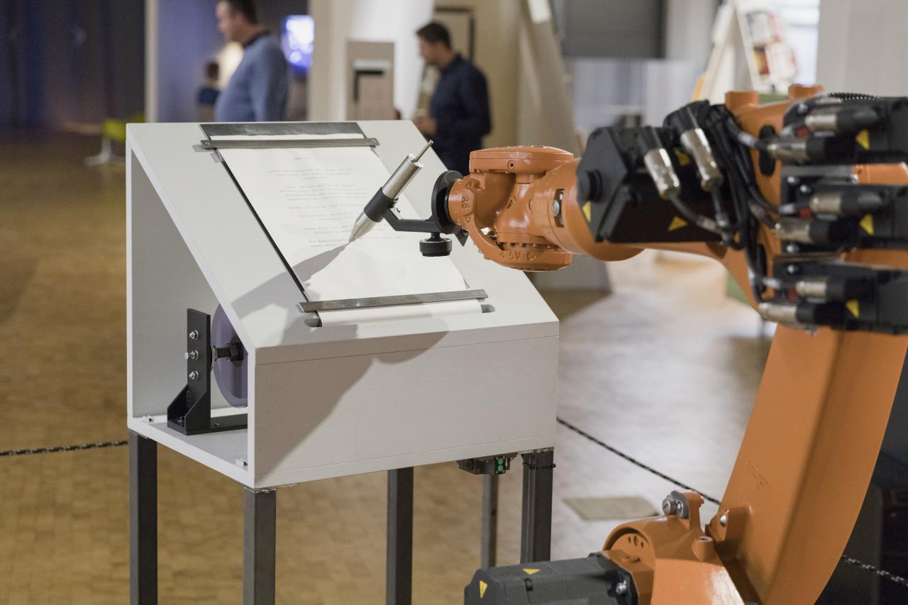 Ein oranger Roboterarm schreibt mit einem großen silbernen Stift auf Papier
