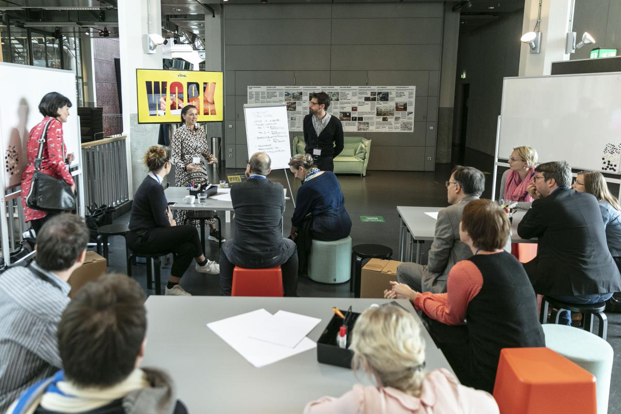 Many people at group tables at a workshop