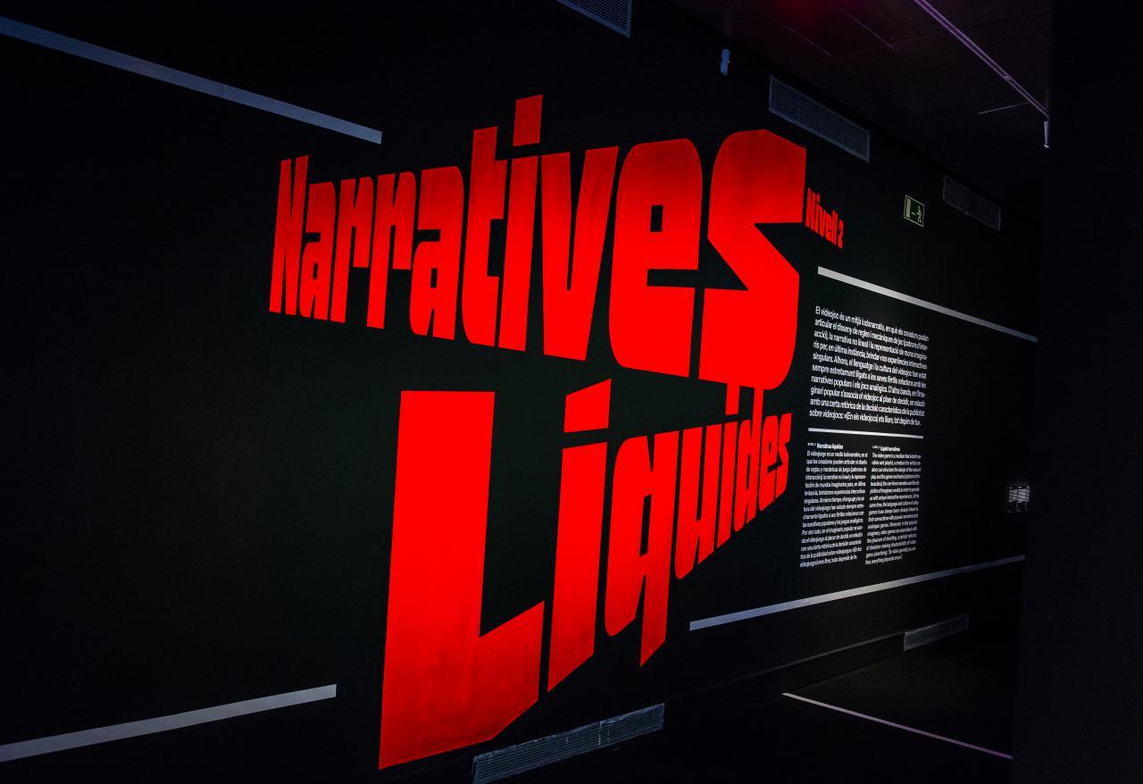 Der Schriftzug »Narratives Liquides« ist in großen roten Buchstaben in schräglage zu sehen. Rechts beginnt der Ausstellungseingang.