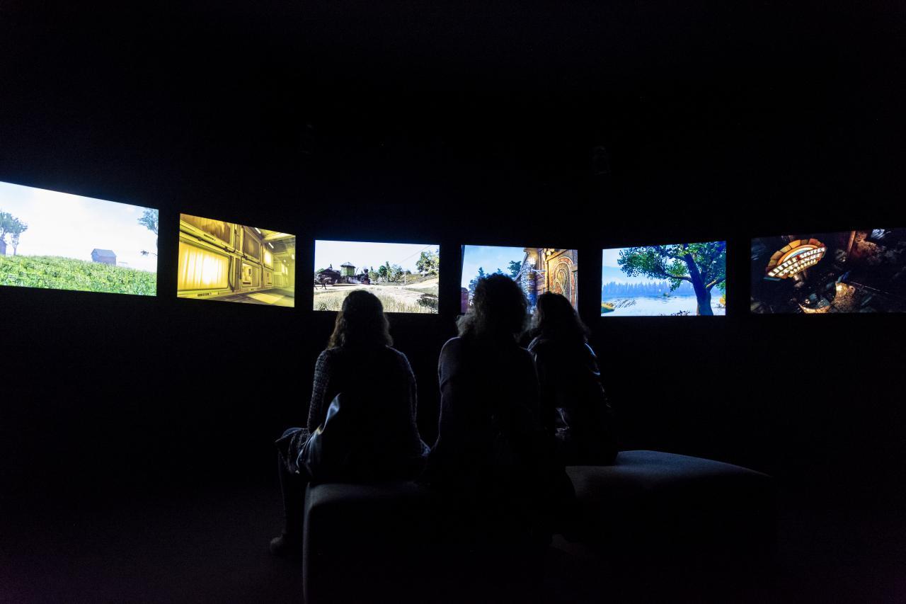 Das Foto zeigt drei Frauen, die in einem dunklen Raum sitzen und deren ausschließlich ihre Silouette zu sehen ist. Im Halbkreis ist eine Bildschirmreihe zu sehen, die die Frauen umgibt.