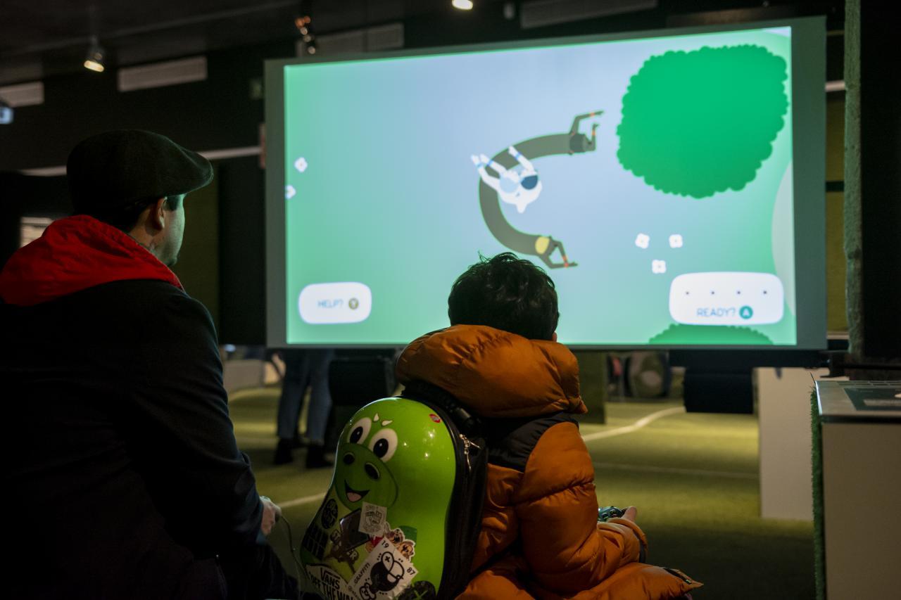 Ein Mann und ein kleiner Junge sind mit dem Rücken zum Betrachter gewandt. Der Junge hat einen birnenförmigen Rucksack an, der einen Computerspielcharakter verkörpert. Im hinteren Teil des Bildes ist ein Bildschirm mit Spiel zu sehen, was gespielt wird.